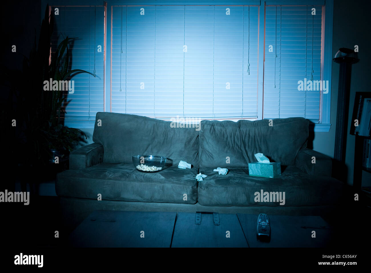 Empty sofa with box of tissues and popcorn - Stock Image