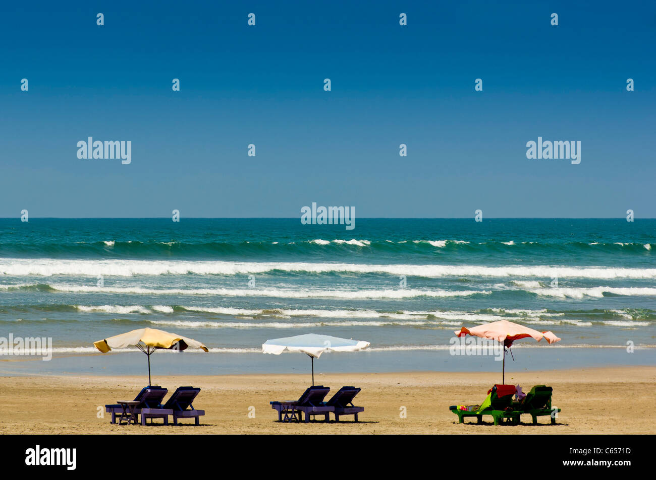 Beach with sun loungers and umbrellas, Bali. Indian ocean in background. - Stock Image