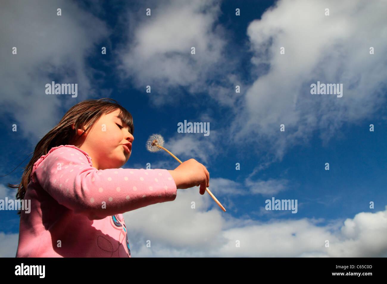 Girl blowing a dandelion clock - Stock Image