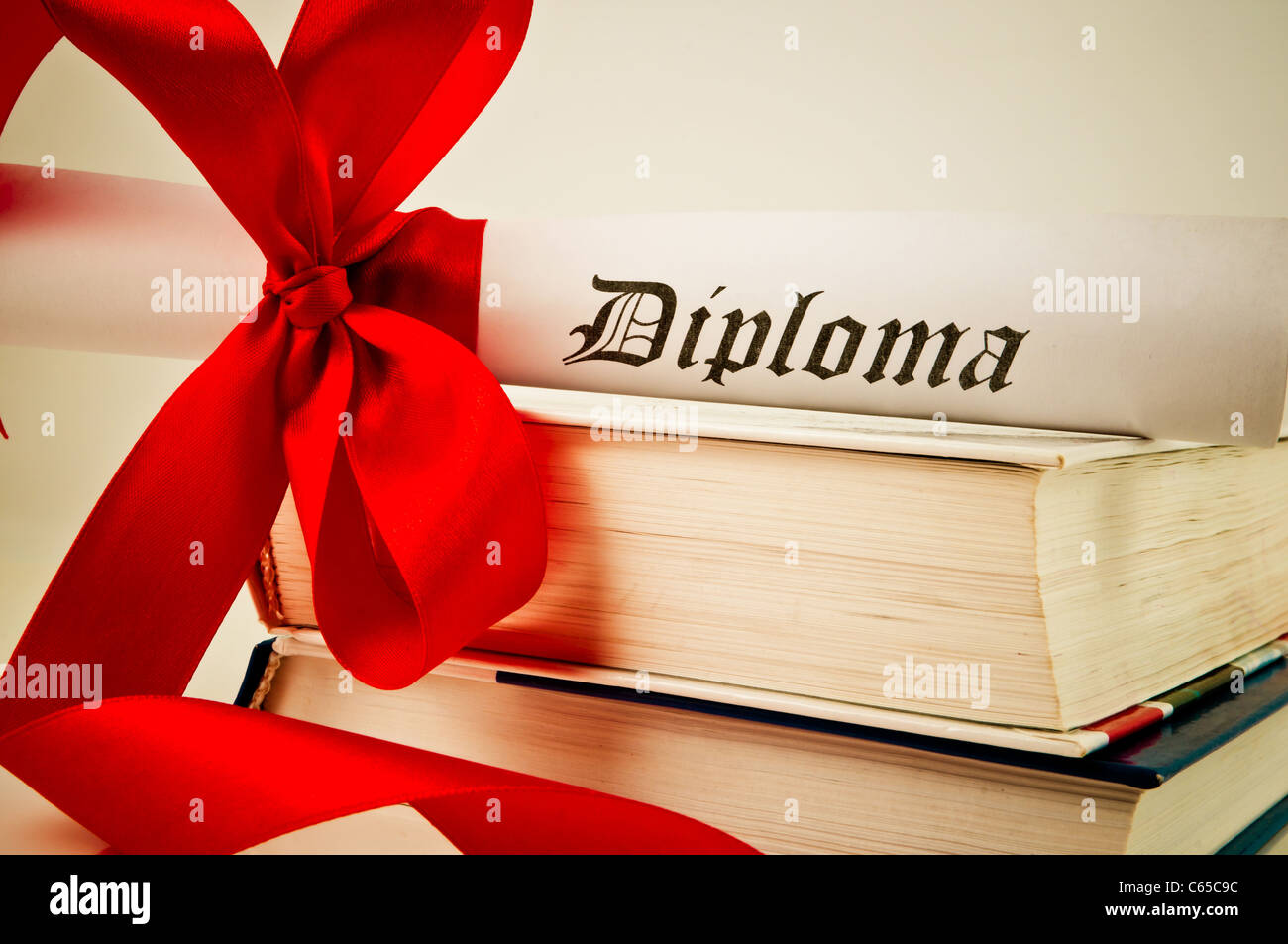 Diploma with red ribbon and books - Stock Image