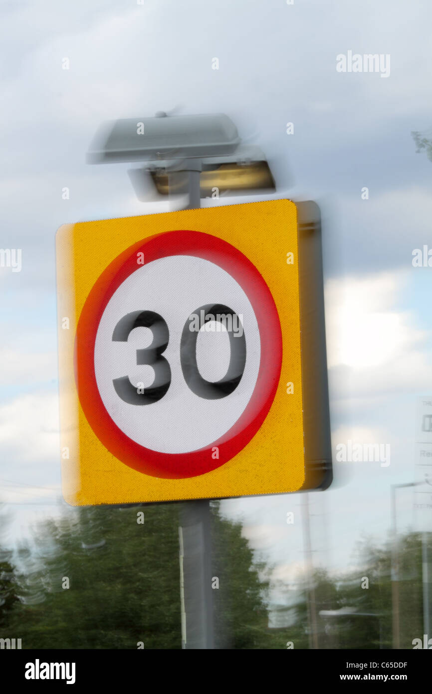 A 30 mph British speed limit sign showing movement to indicate excess speed - Stock Image