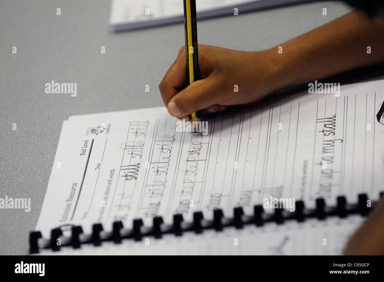Afro-Caribbean school student hand practicing writing basic English with pencil on lined paper - Stock Image