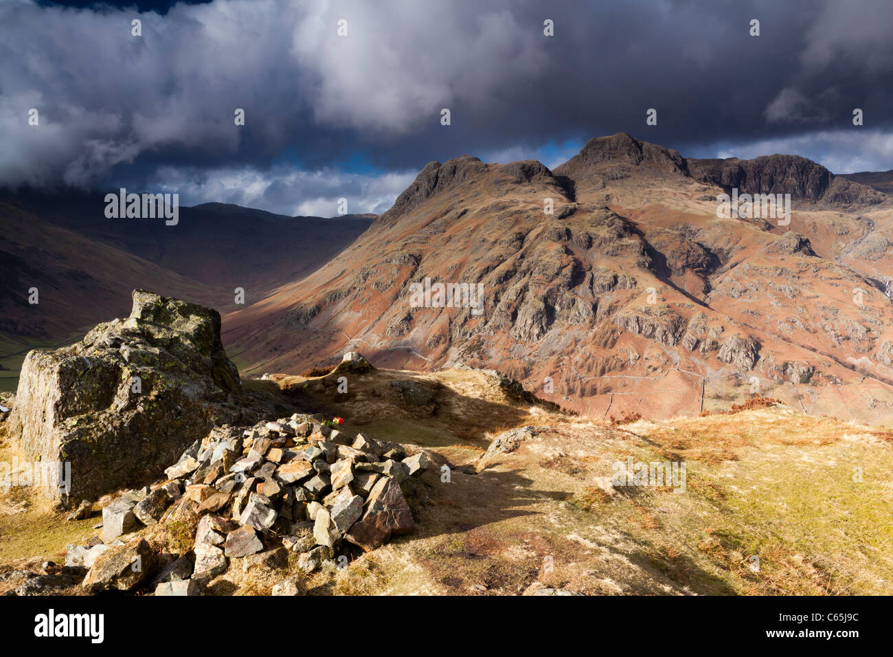 The Langdale Pikes under heavy skies. - Stock Image