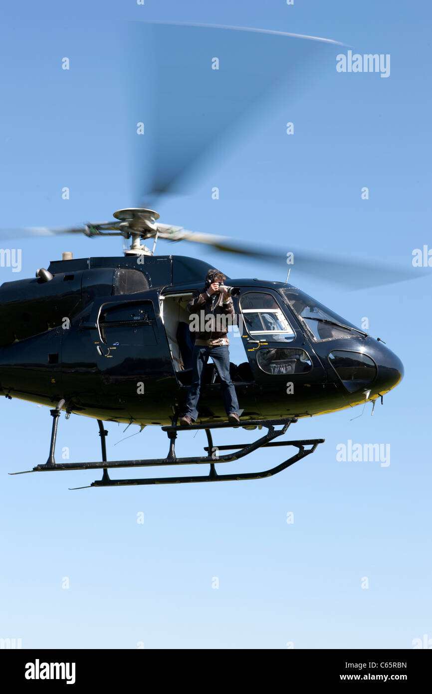 A man hanging from a helicopter taking pictures or doing Aerial photography - Stock Image