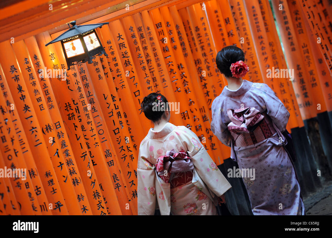 Two Japanese women wearing kimonos walk past torii or red gates, lining a path at Fushimi Inari shrine near Kyoto. - Stock Image
