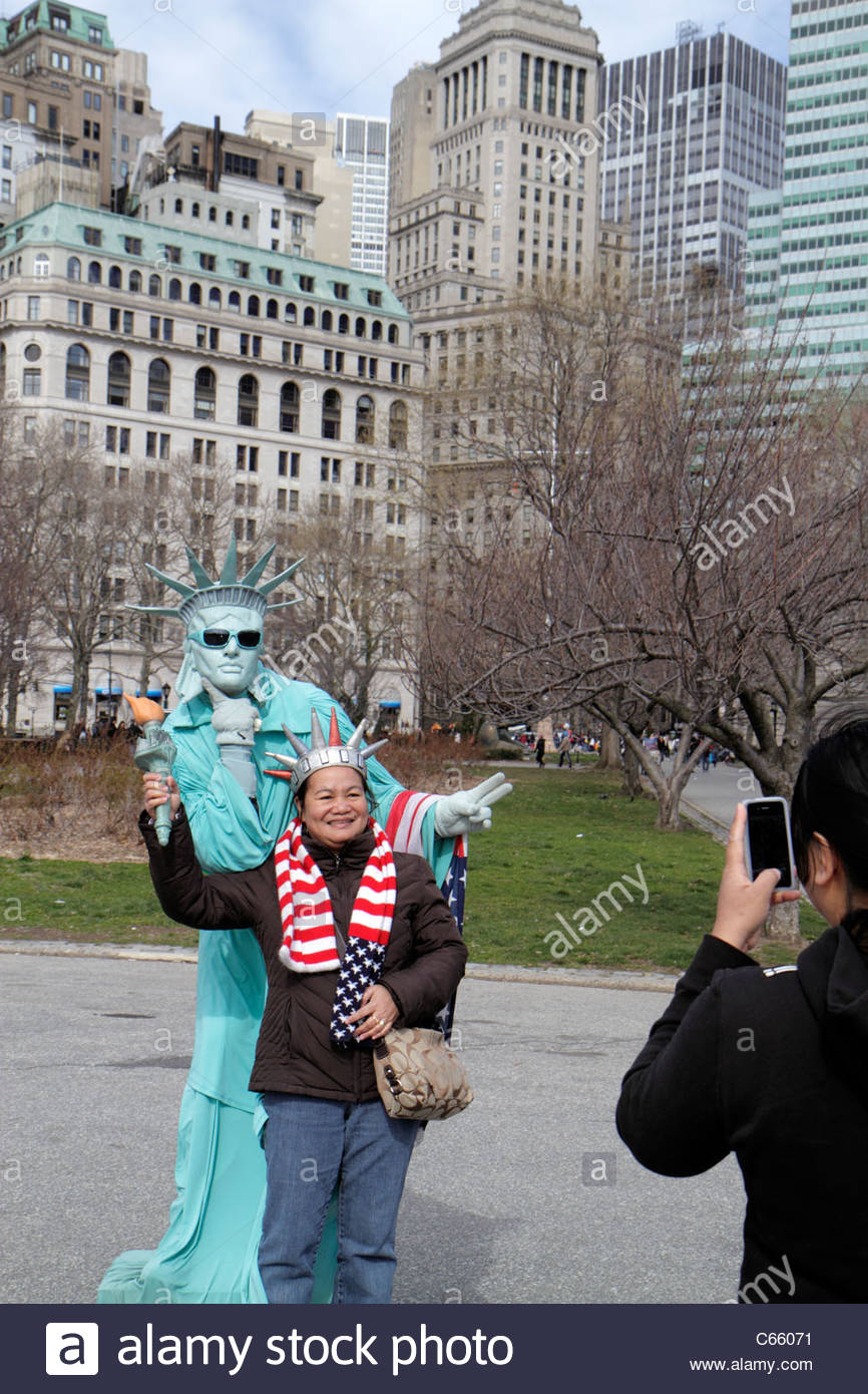 Lower Manhattan New York City NYC NY Battery Park street performer busker mime living statue Statue of Liberty Asian - Stock Image