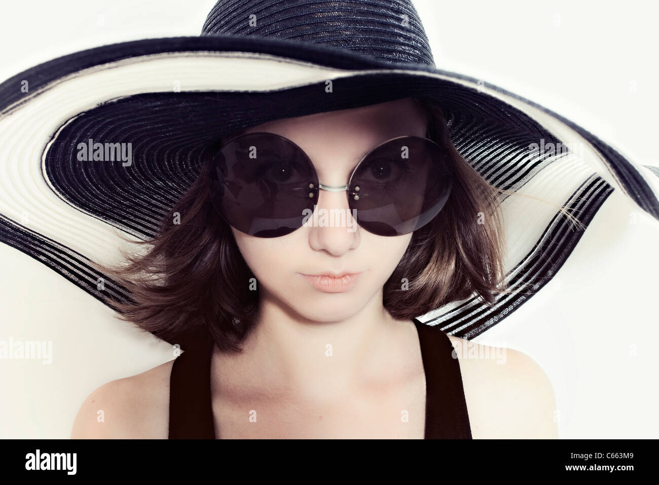 78f9bded30 Portrait of a young girl in a big round sunglasses and summer hat ...