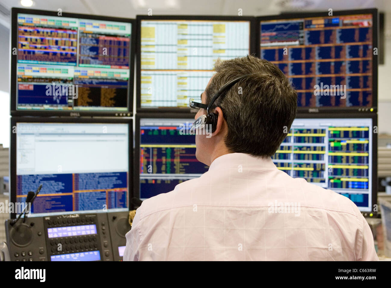A trader wearing a headset watches his computer screens. - Stock Image