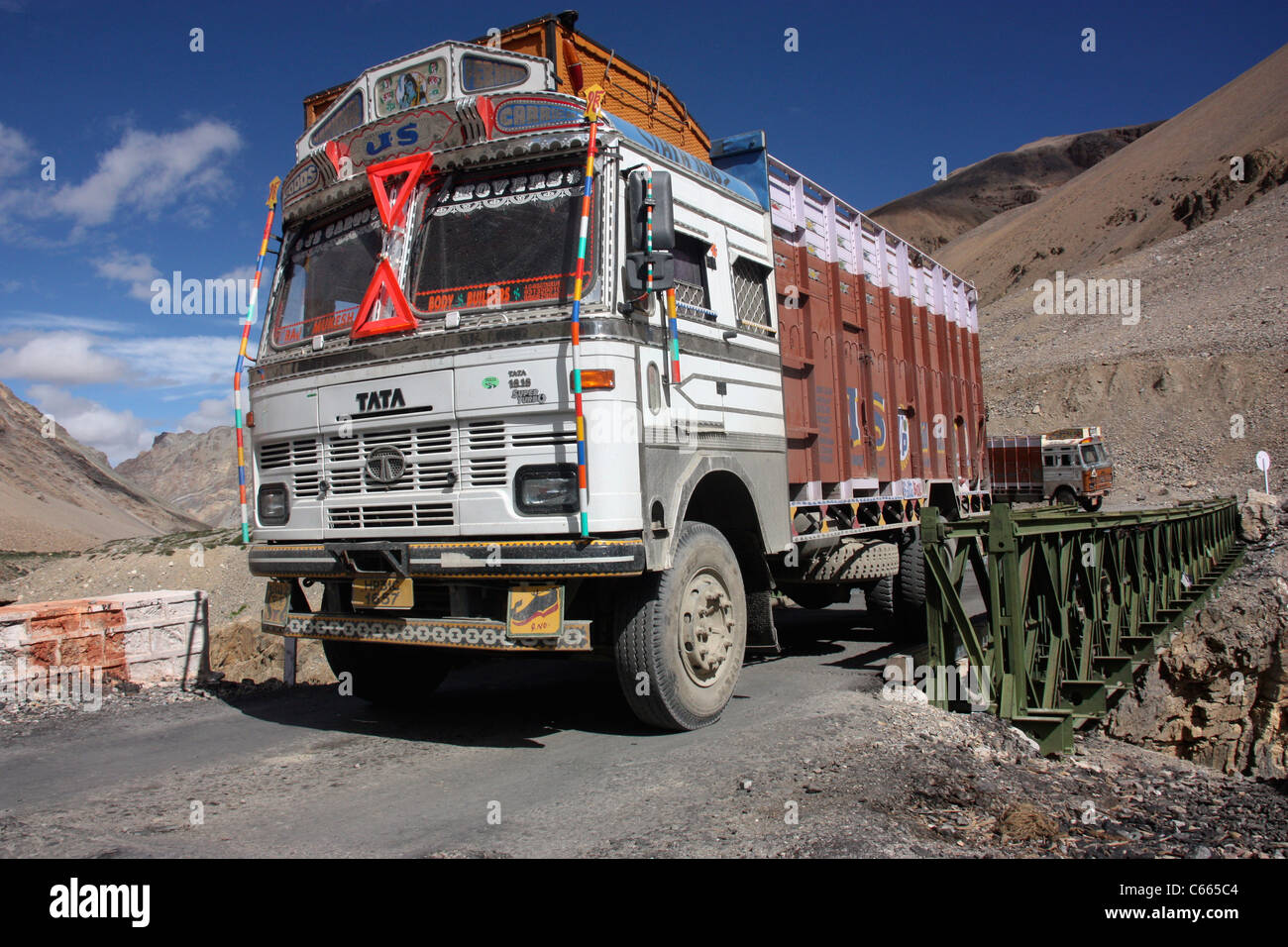 Decorated Tata 1613 truck crossing a bridge in the Himalayas on the  hazardous road to Leh, Ladakh northern India