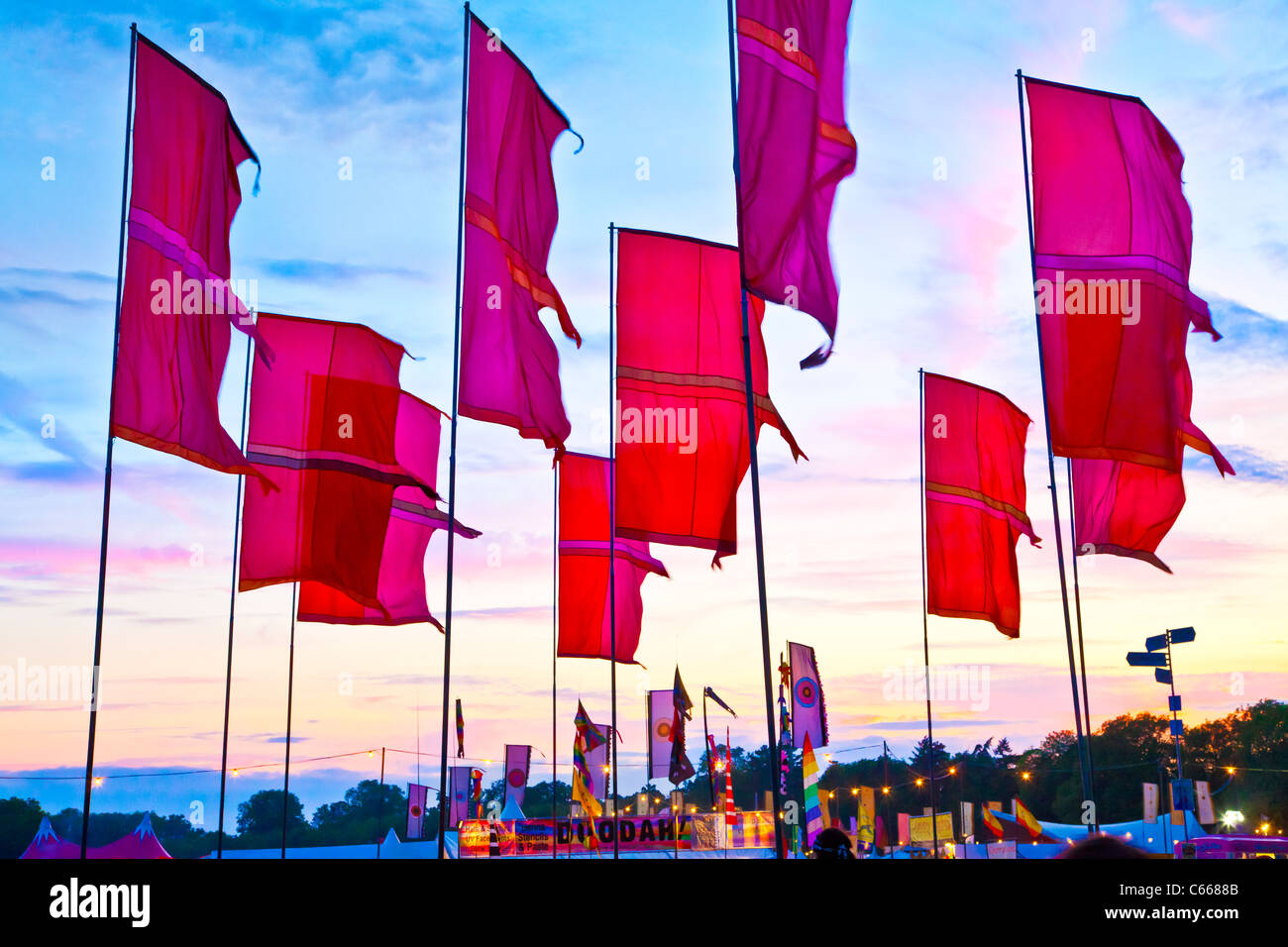 Festival flags at twilight at WOMAD 2011, Charlton Park, Malmesbury, Wiltshire, England, UK - Stock Image