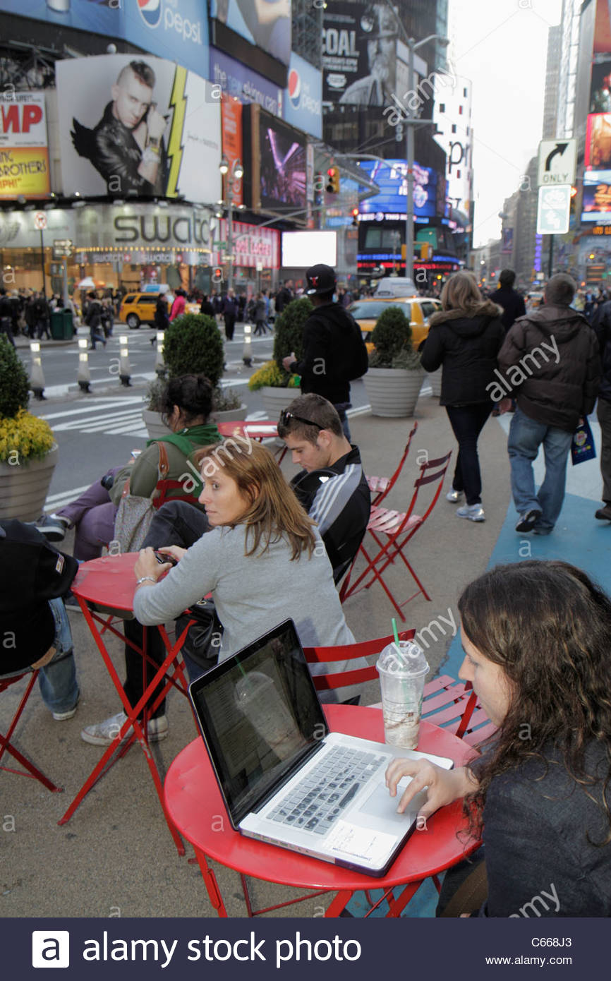 New York New York City NYC Midtown Manhattan Times Square Theatre District woman pedestrian plaza table outdoor - Stock Image