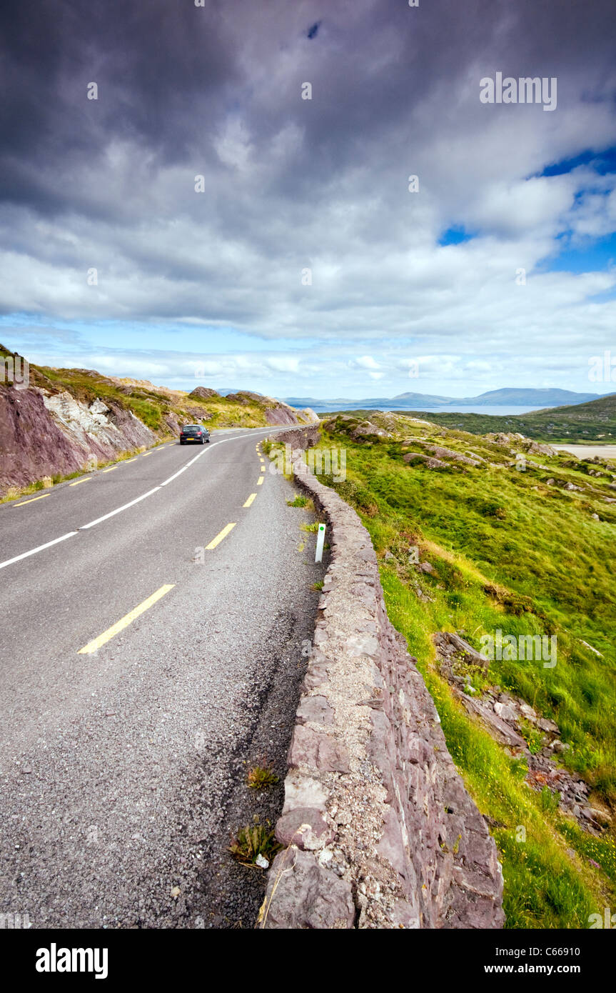 A car driving along the Ring of Kerry near Waterville in County Kerry, Ireland - Stock Image
