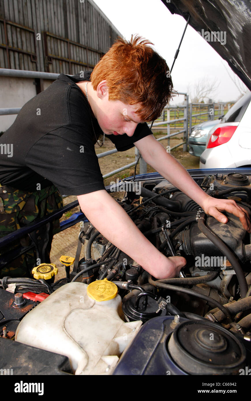 Youth learning car mechanic skills at an initiative to foster teamwork and confidence skills amongst disadvantaged Stock Photo
