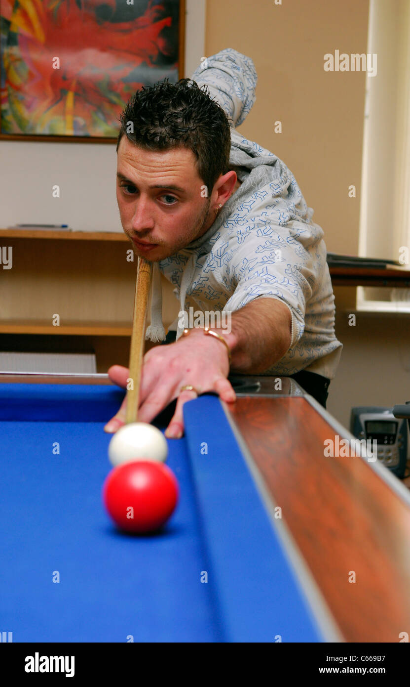 Young man playing pool at a YMCA, Hertfordshire, UK. - Stock Image