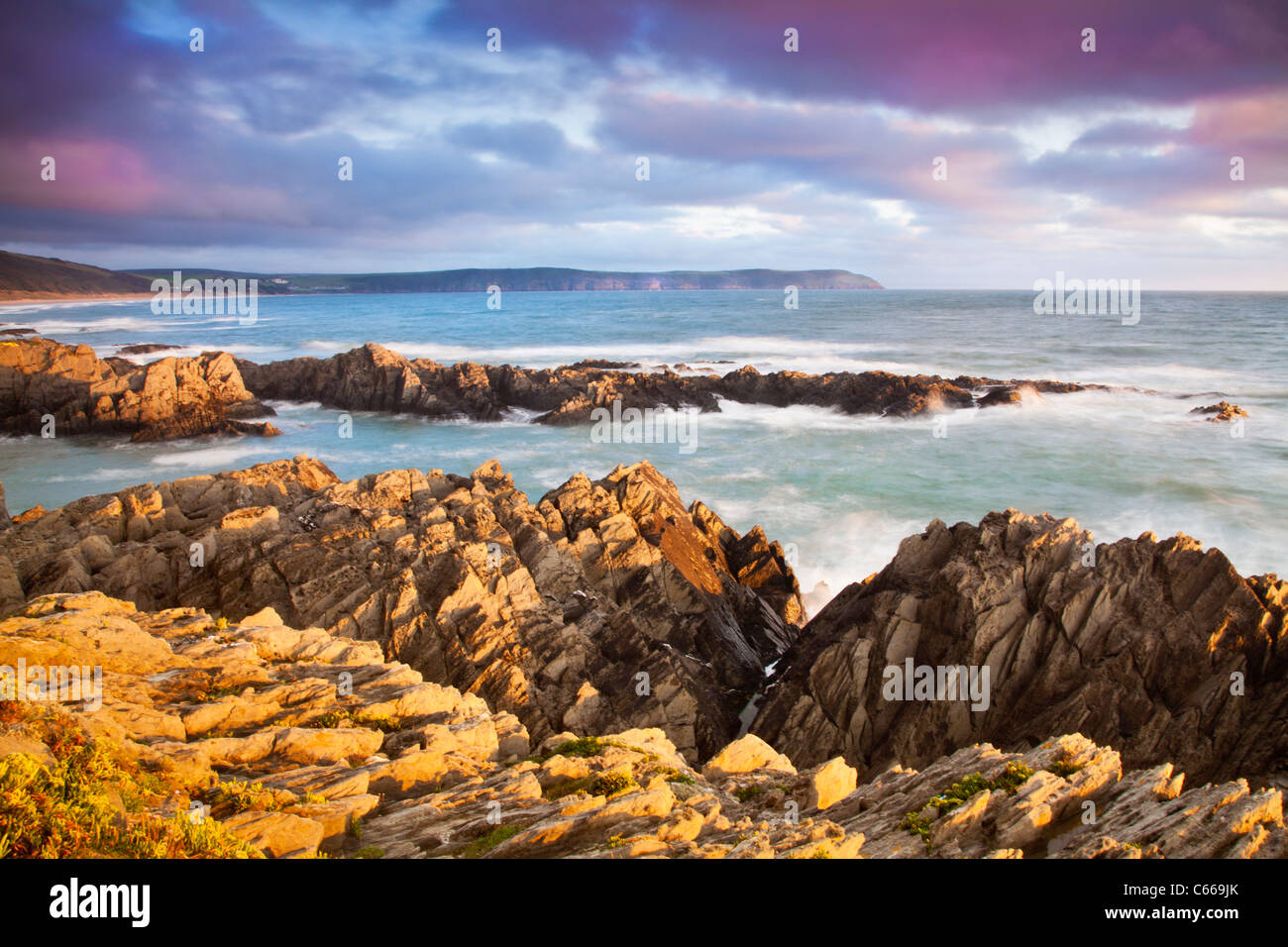 Evening light falls on the rocks of Barricane Beach, Woolacombe,looking towards Baggy Point, North Devon, England, - Stock Image