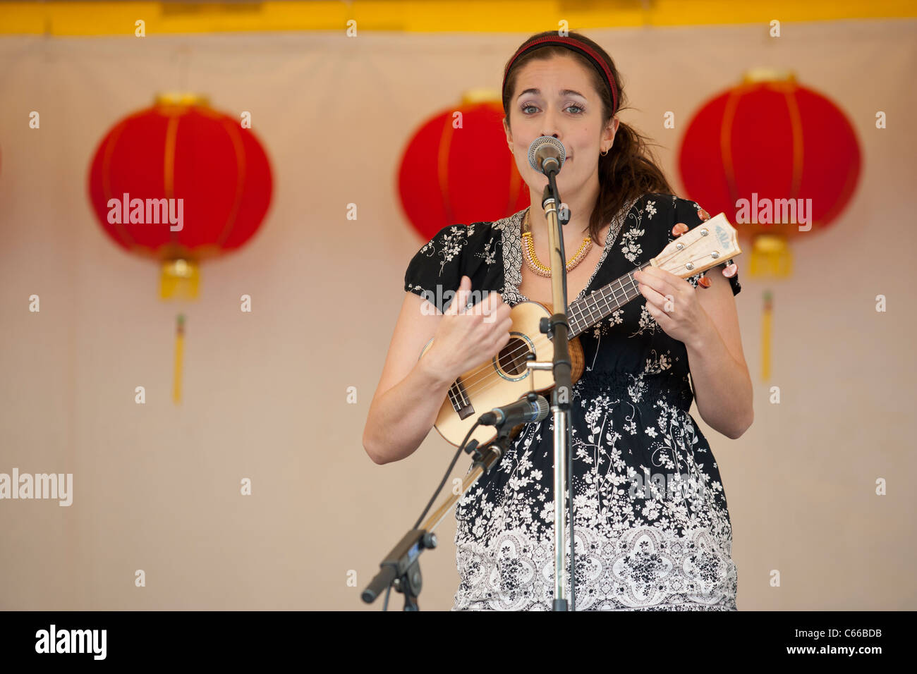 Female singer playing ukelele and singing at Dragon Boat festival-Victoria, British Columbia, Canada. - Stock Image