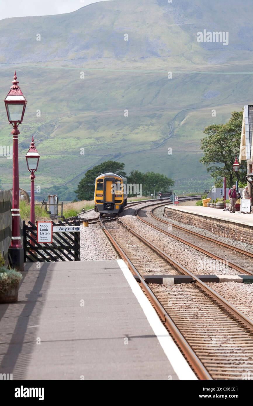 Train heading northwards on the Settle to Carlisle line out of Ribblehead station approaching Ribblehead viaduct - Stock Image