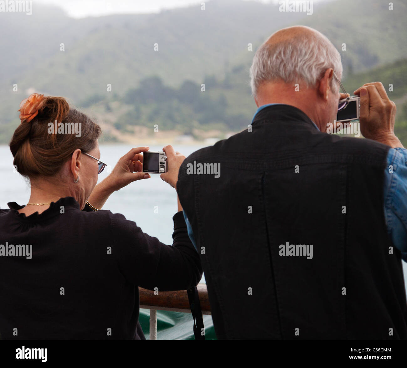 A mature couple, people, taking photographs using compact cameras. - Stock Image