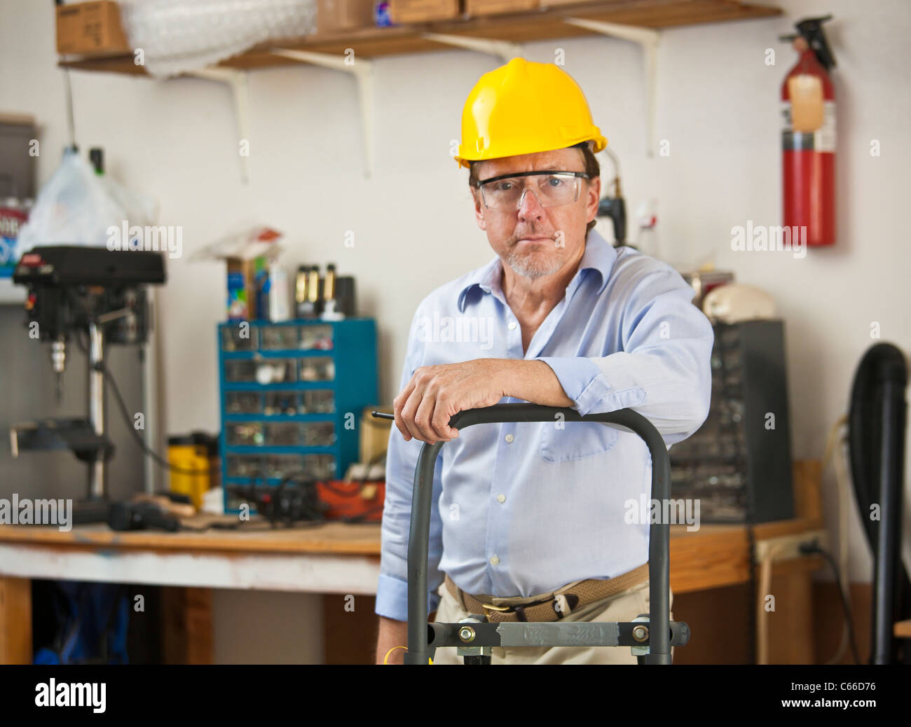 d8926f32894 man wearing yellow hard hat in work shop with hand truck Stock Photo ...