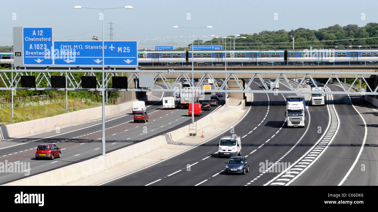 Railway bridge and train crossing Junction 28 of the M25 UK motorway with signs - Stock Image