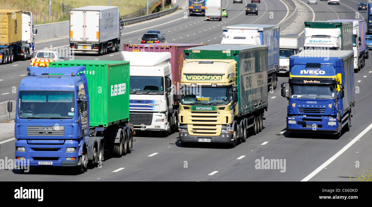 Transport lorry truck four lanes section of M25 motorway close up vehicles overtaking slower hgv lorries & trucks Stock Photo