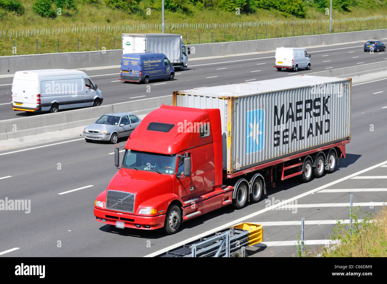 HGV Volvo lorry truck & articulated trailer loaded Maersk shipping container driving along motorway (company - Stock Image