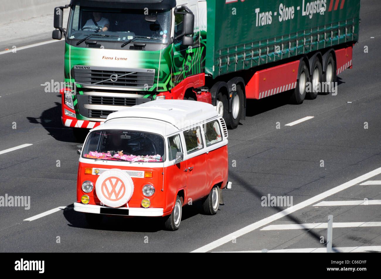 Classic Volkswagen VW Camper van on UK motorway (obscured numberplate) front mounted spare tyre with VW logo England - Stock Image