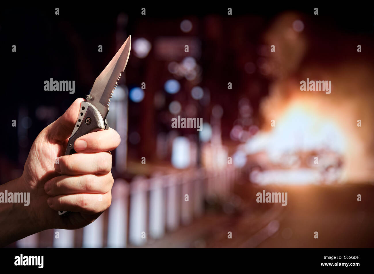Hand holding a knife with a serrated edge while a car burns in the background. London UK - Stock Image