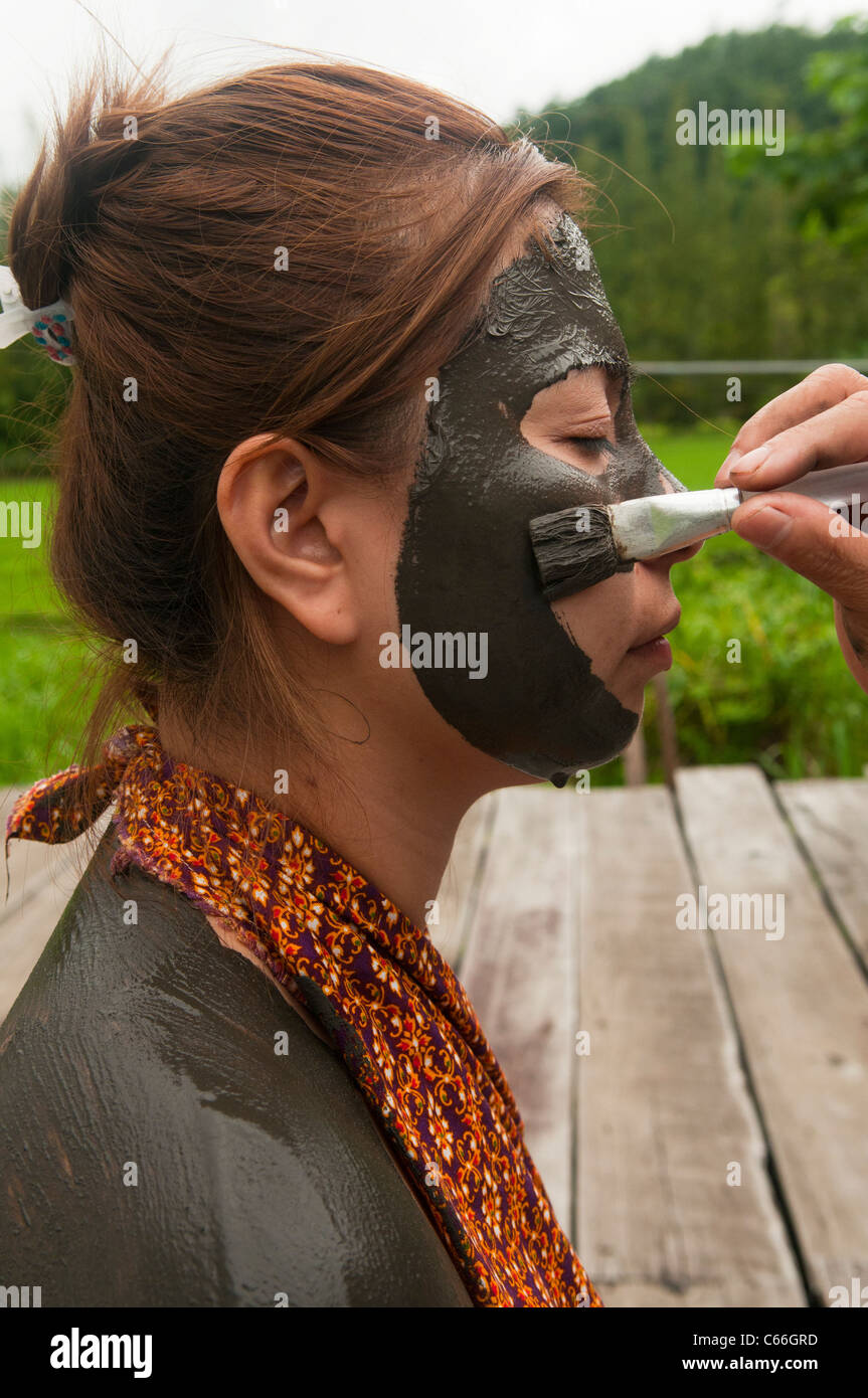 Thai woman enjoying a therapeutic mud treatment at the Phu Klon Mud Spa in Mae Hong Son, Thailand - Stock Image
