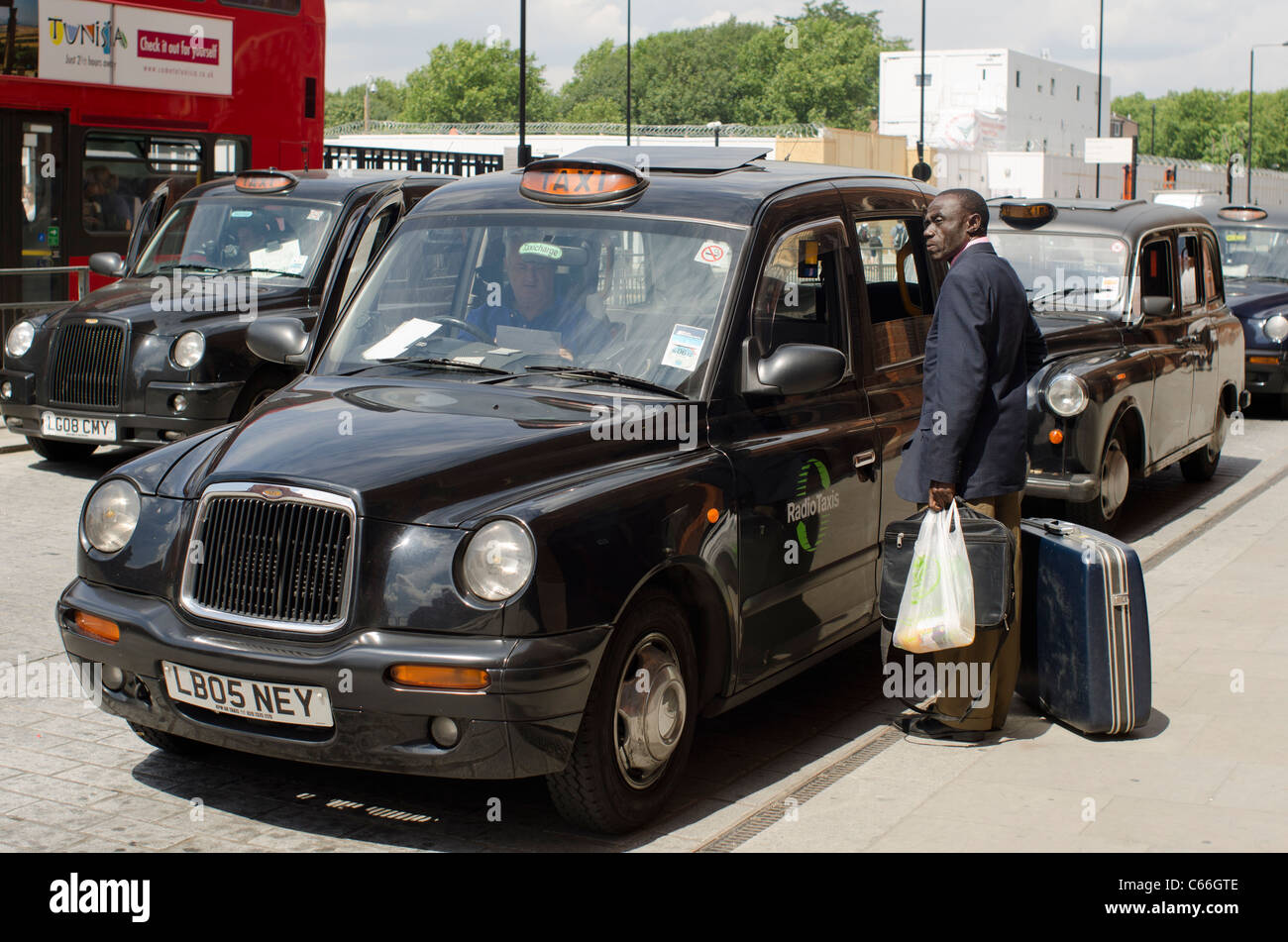 Gentleman waiting outside a Black Cab in London, England. - Stock Image