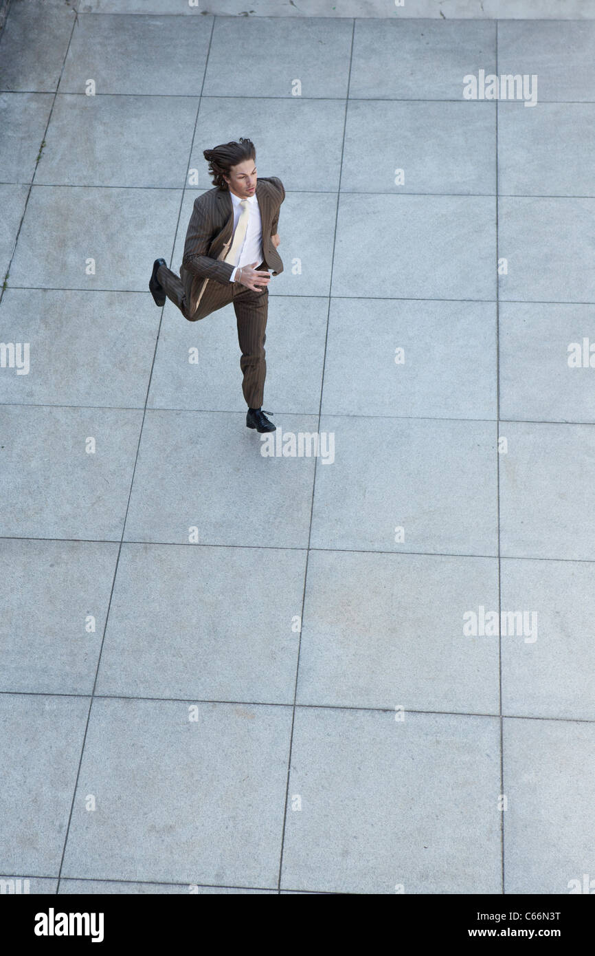 Businessman running in square - Stock Image