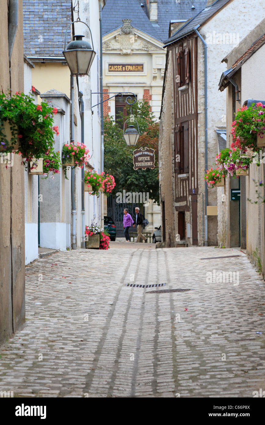 Two people on a narrow cobbled flower lined street in the medieval town of Beaugency Loire Valley France - Stock Image