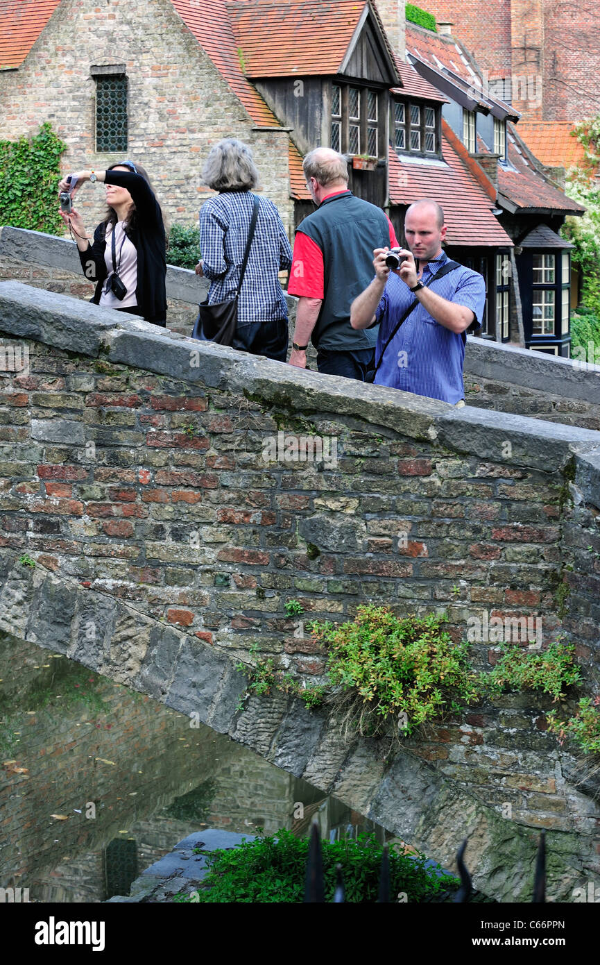 Tourists with cameras taking pictures from the Bonifacius bridge over canal in Bruges, Belgium - Stock Image