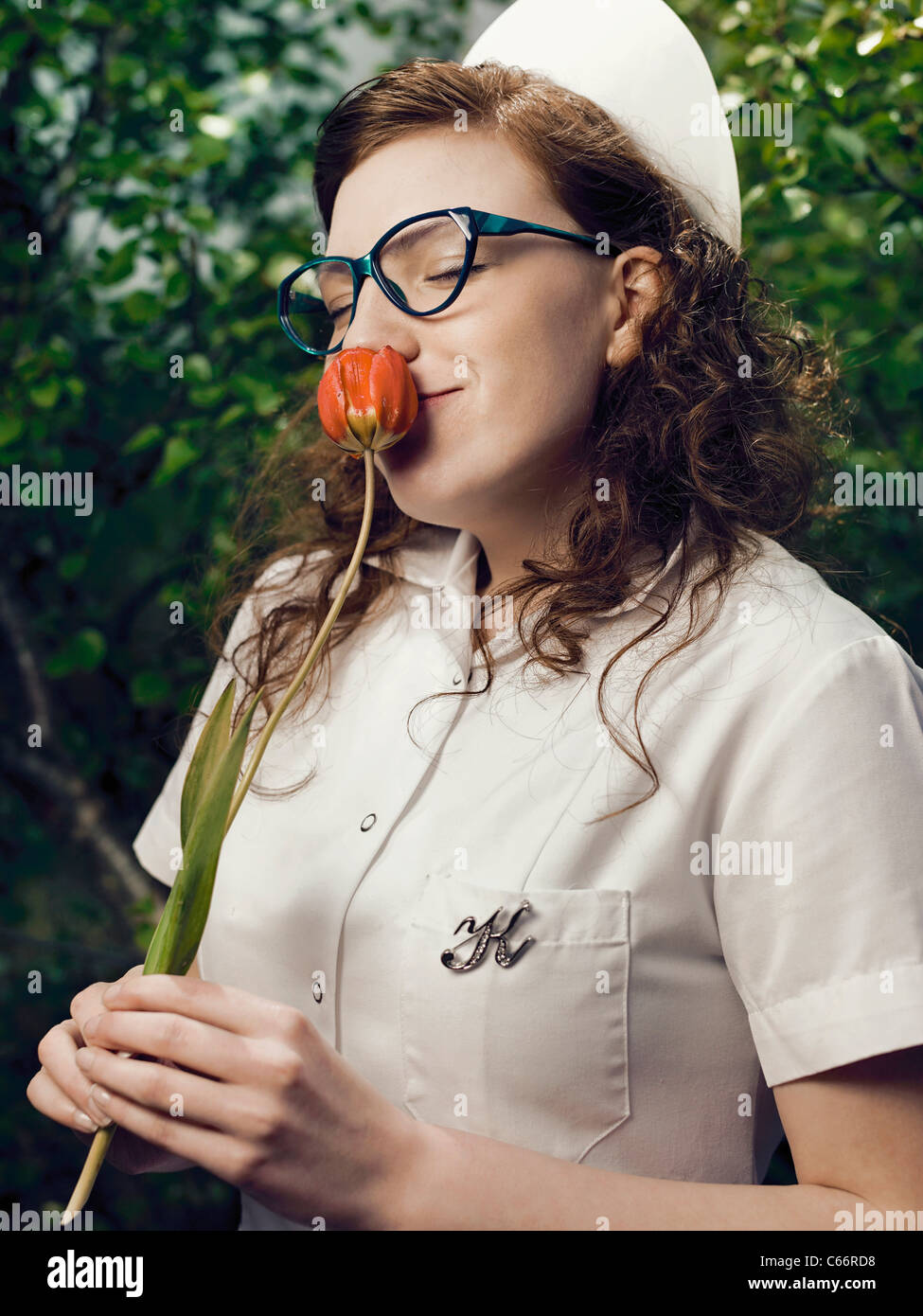 Nurse in glasses smelling flower Stock Photo