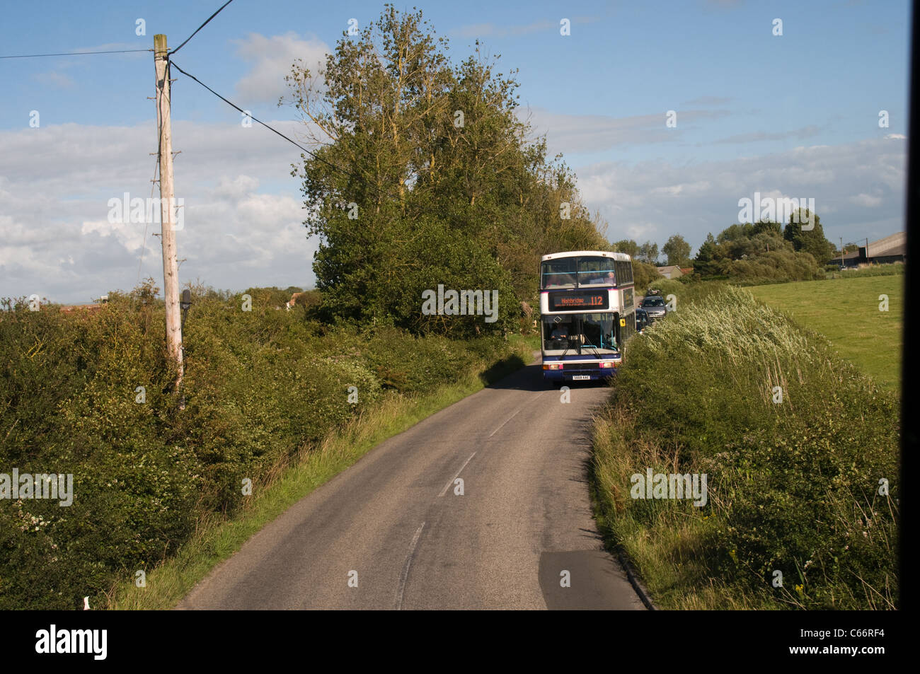 A double deck bus traveling down a  country road has pulled over to the nearside to allow a bus traveling the other - Stock Image
