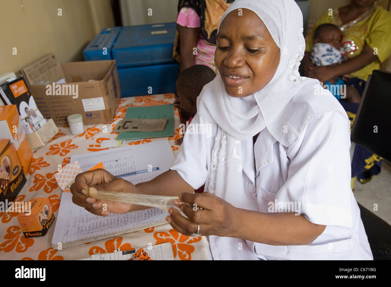 A woman demonstrates the use of a condom in a family planning clinic in Dar es Salaam, Tanzania, East Africa. - Stock Image