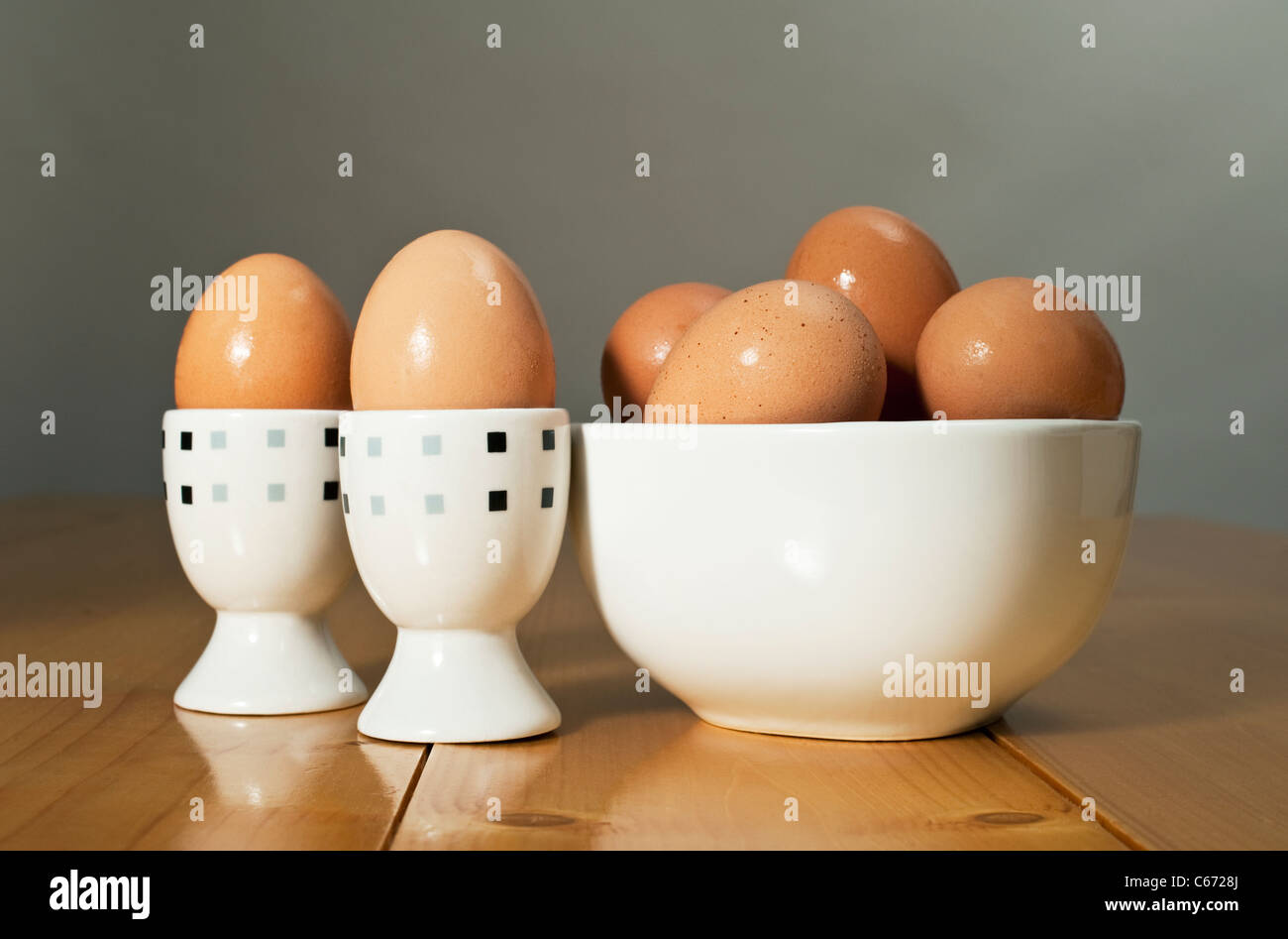 Two Boiled eggs with other eggs in a white bowl - Stock Image