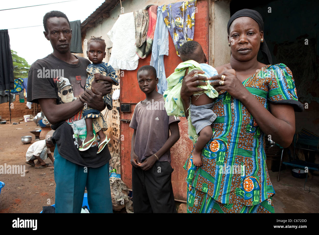A family stands outside their house in a slum in Bamako, Mali, West Africa. - Stock Image