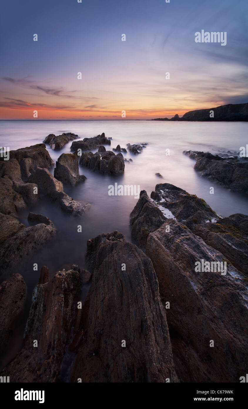 Rocky seashore at dusk near Thurlestone, Devon - Stock Image
