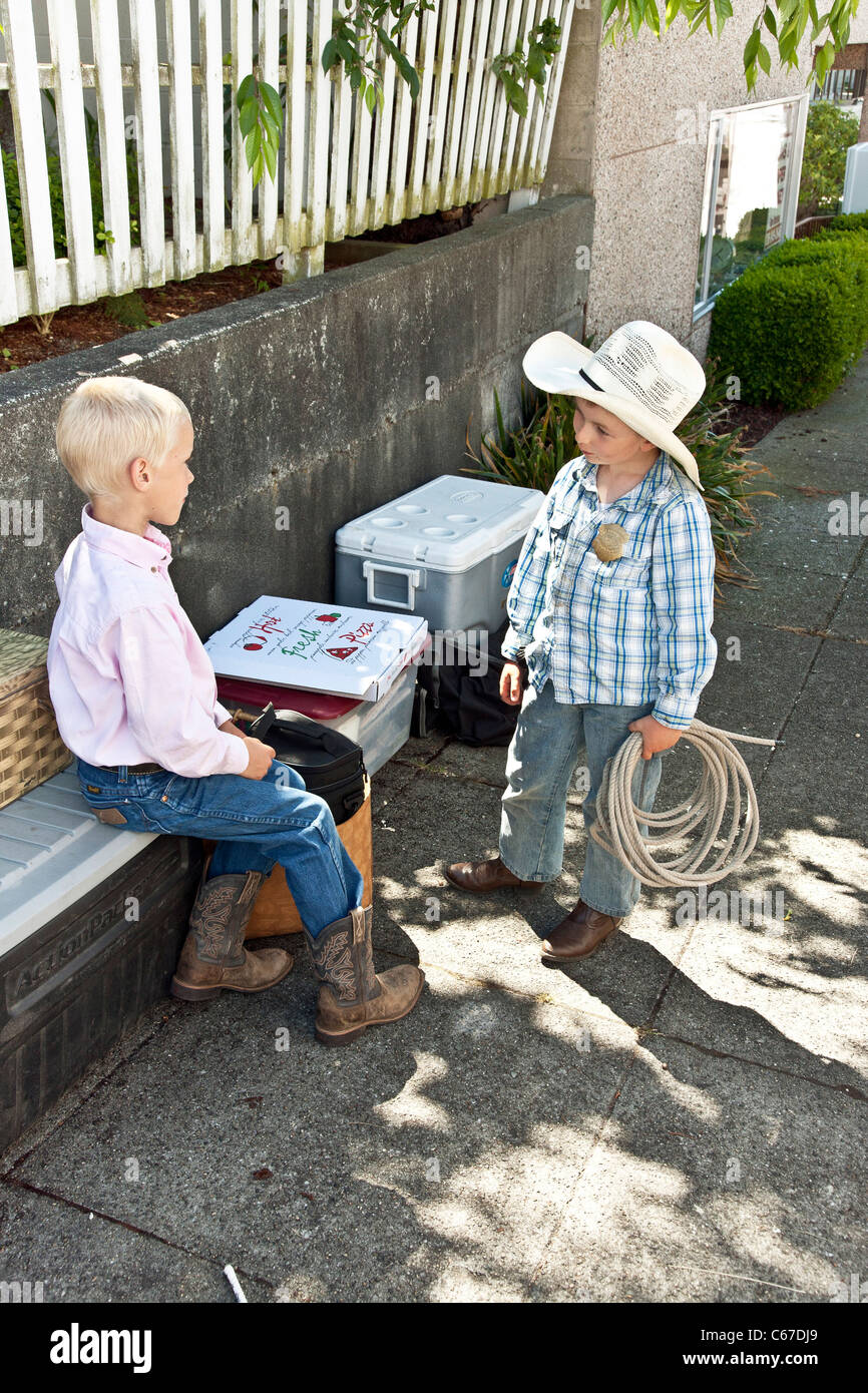 a very young cowboy in authentic western dress holding coiled rope discusses coiling ropes with his older brother - Stock Image
