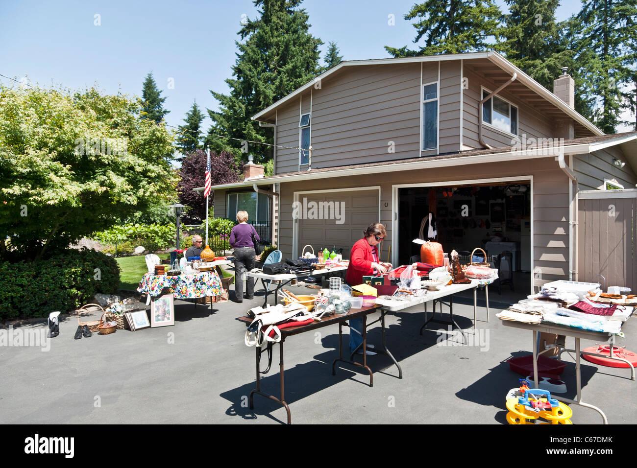 garage yard sale used clothes artwork dishes bric a brac kitsch in driveway outside suburban house Edmonds Washington - Stock Image