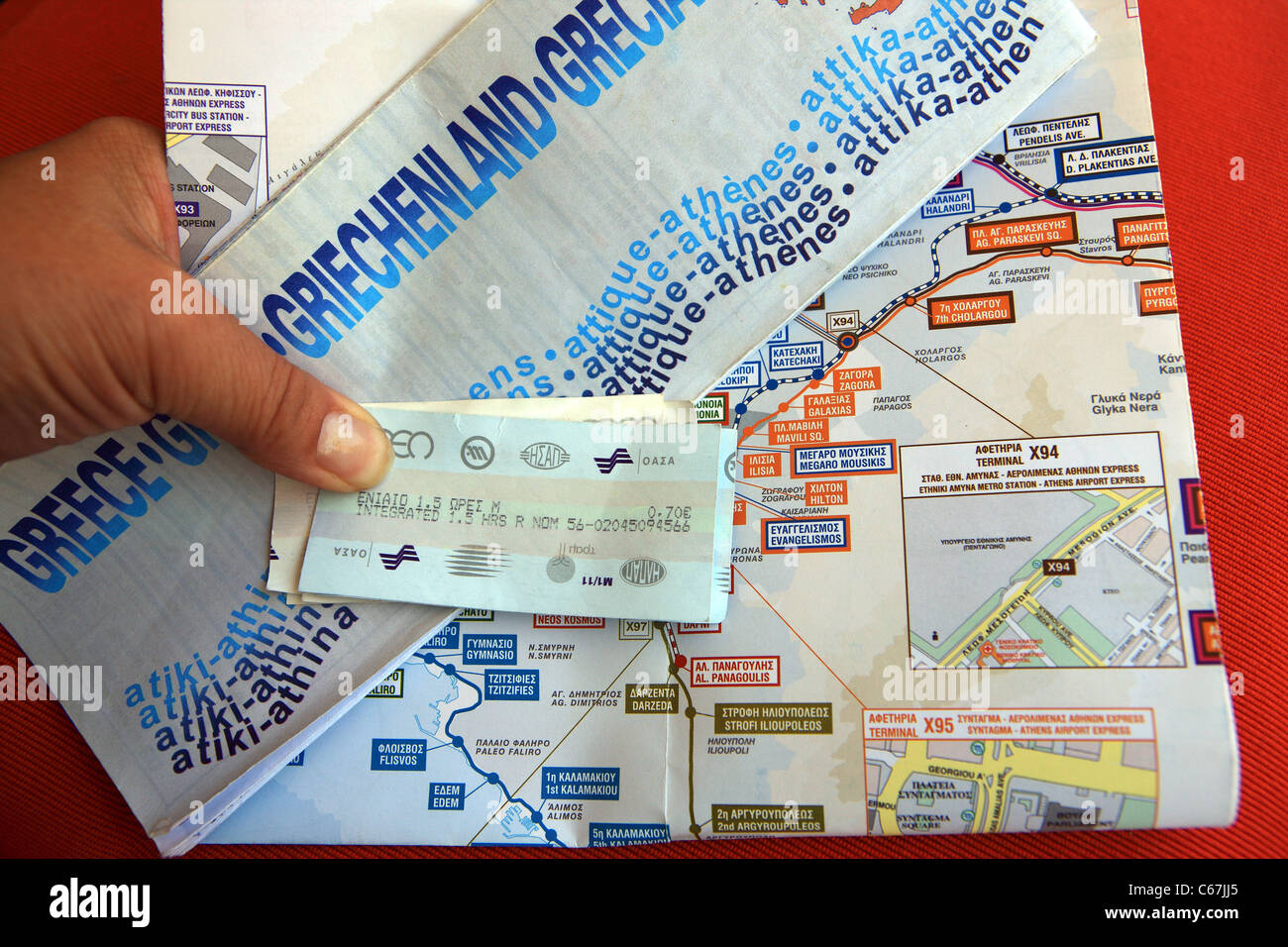 Tourist hand holding a map of Athens and metro tickets and map - Stock Image