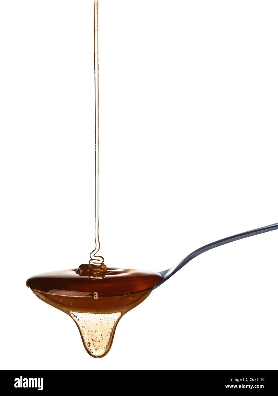 The honey slowly falls onto the spoon. - Stock Image