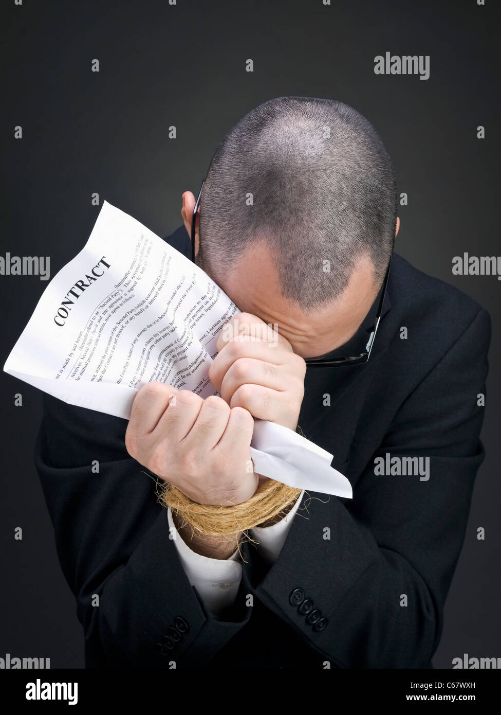 A man on a suit holds a contract on his tied hands. - Stock Image