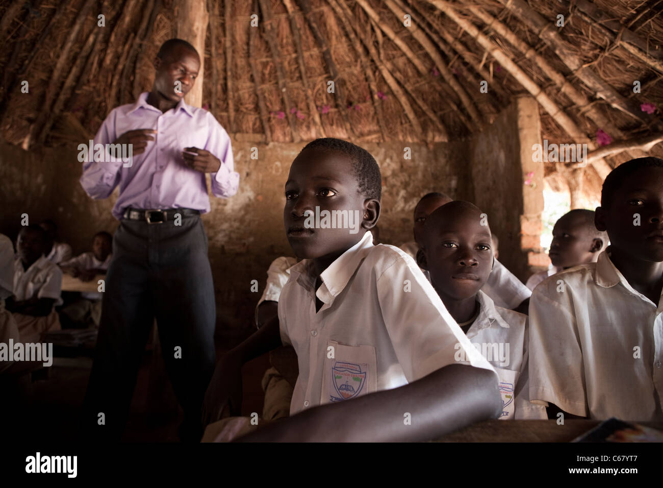 A teacher teaches in a grass roof classroom in Amuria, Uganda, East Africa. - Stock Image