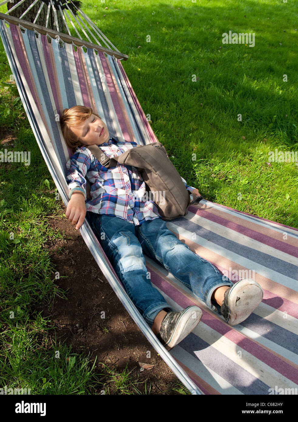 Young boy resting in a hammock after a day in school - Stock Image