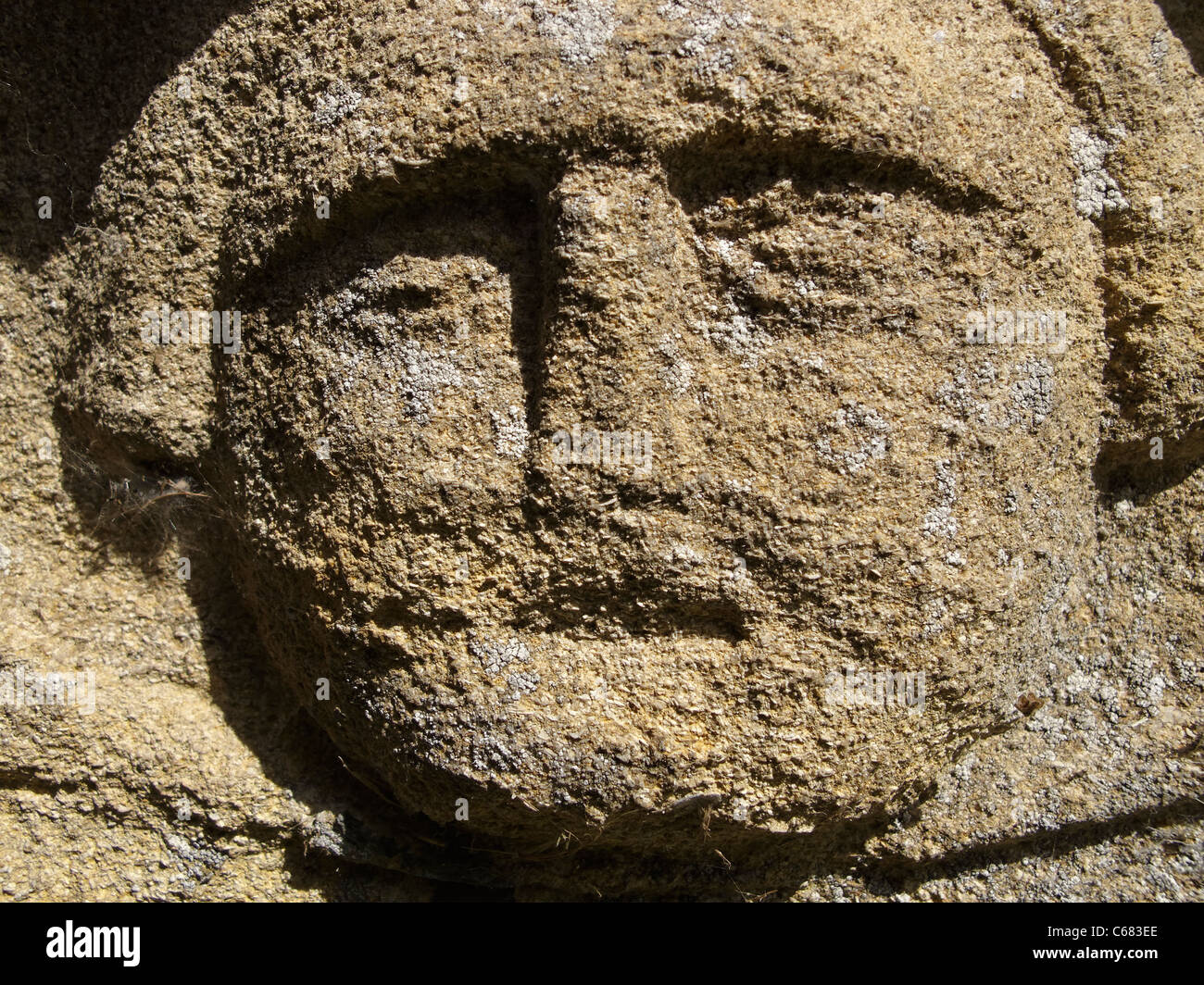 An old carved headstone depicting a face at St Wilfrid's church, Honington, Lincolnshire, England. - Stock Image