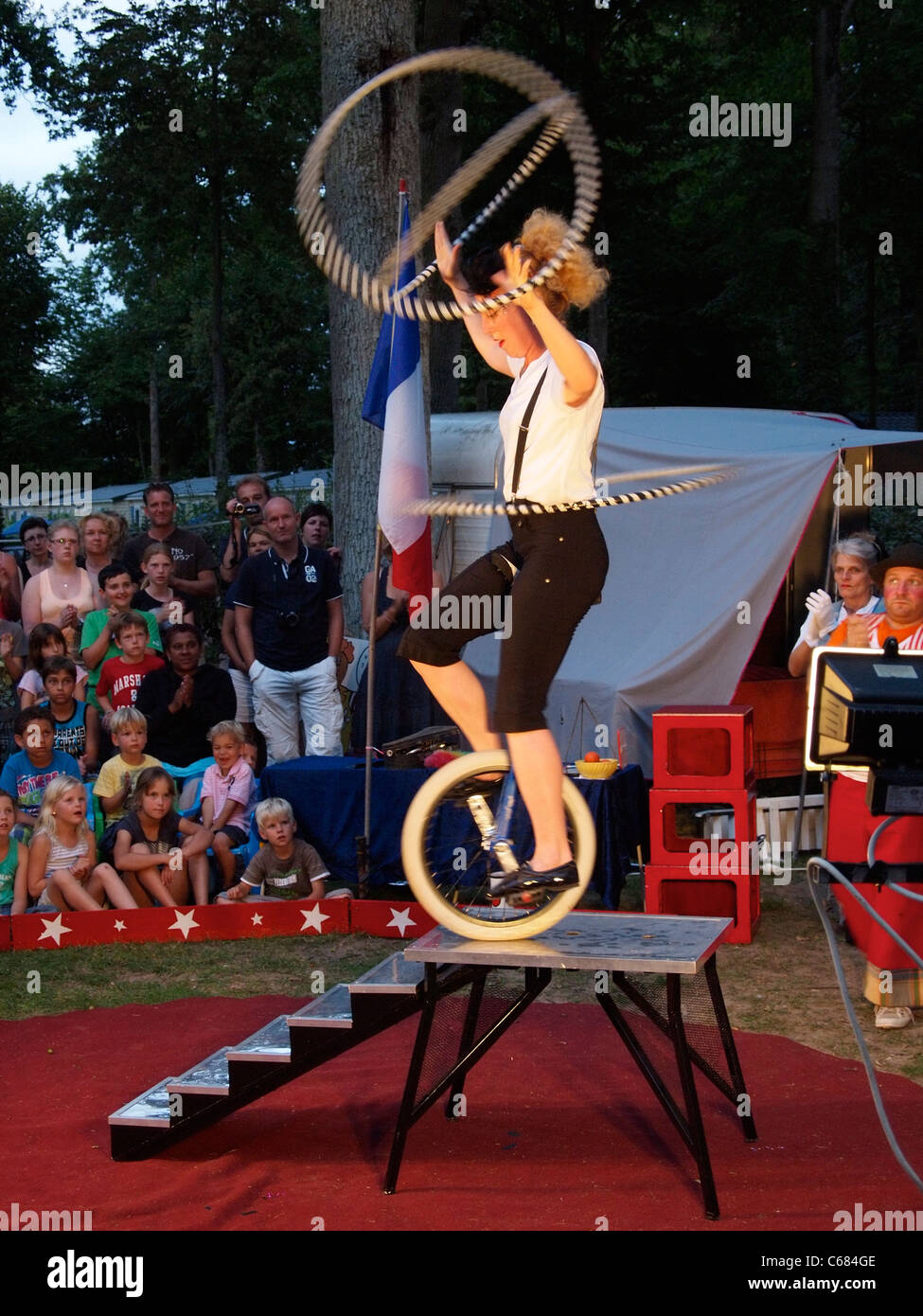 Female acrobat on unicycle in a small open air circus, performing on a camping site in Mer, France - Stock Image