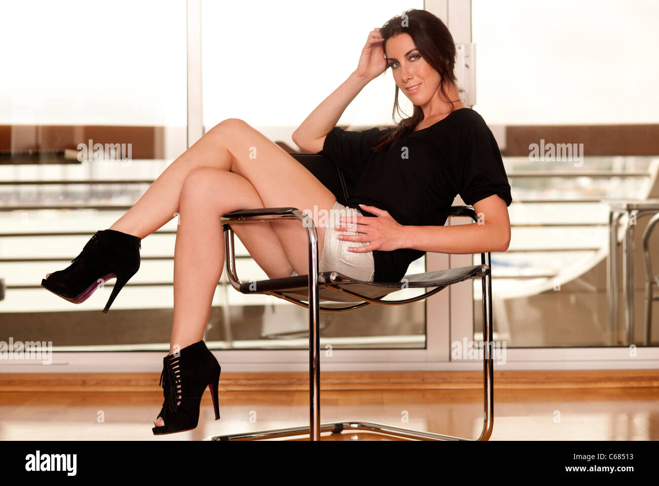 woman sitting on a chair with legs crossed , sexy with high heeled