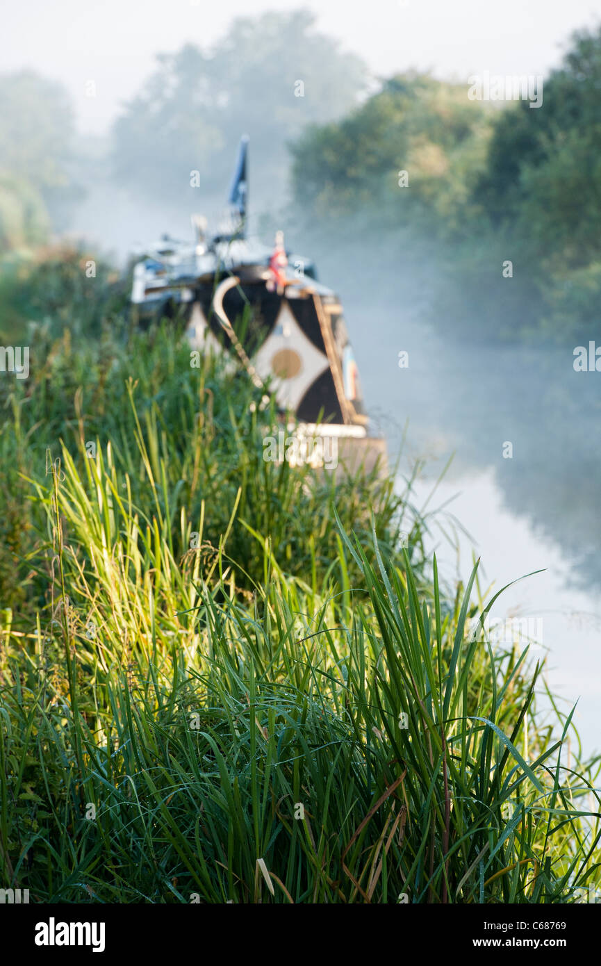 Towpath Grass in front of Canal boat at Aynho Wharf on a misty morning. Oxfordshire, England - Stock Image